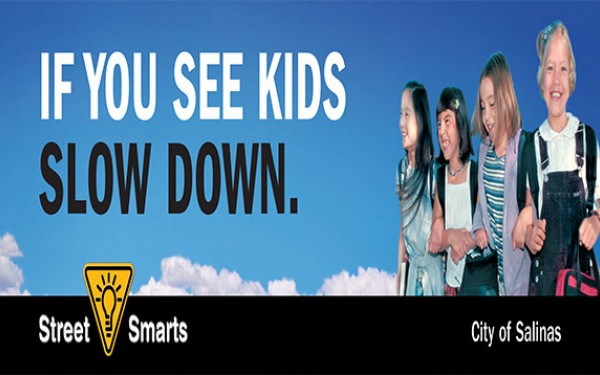 If You See Kids Slow Down, four children smiling, blue sky
