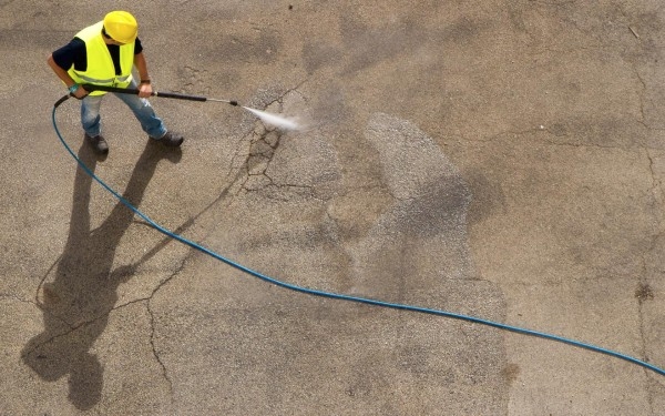 Worker power washing street surface