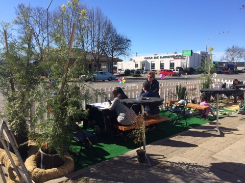 Kids play in a temporary parklet in front of Leal Bakery