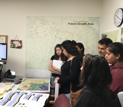 Young students reviewing planning maps and materials