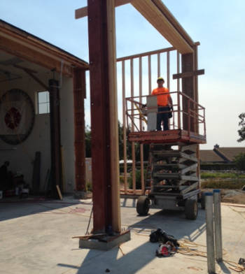 Construction worker in lift working on girder beams at new Salinas Fire station